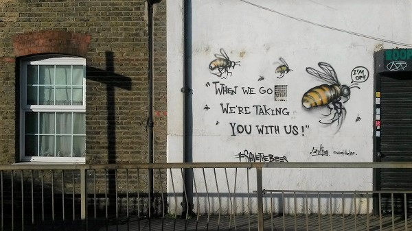 """When we go, we're taking you with us"" graffiti with bees"